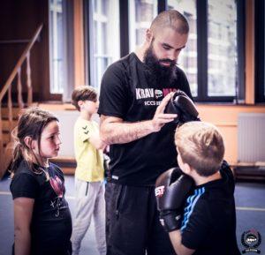 deux enfants occupés d'apprendre à frapper avec le coach
