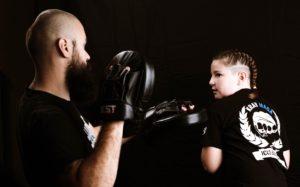 une enfant boxe sur patte d'ours avec le coach